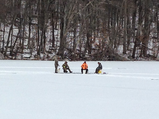 Photo of small ice-fishing party on snow-covered lake