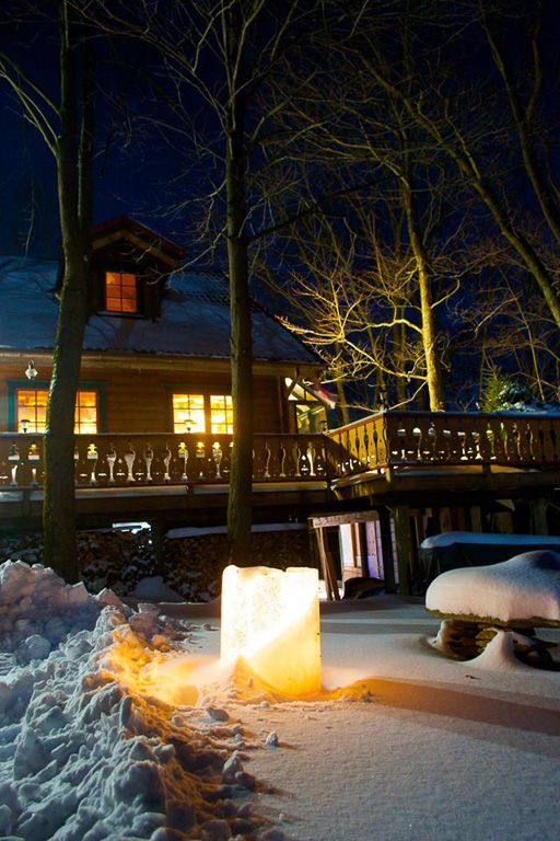 Night photo of candle in snow with warm, inviting house in the background